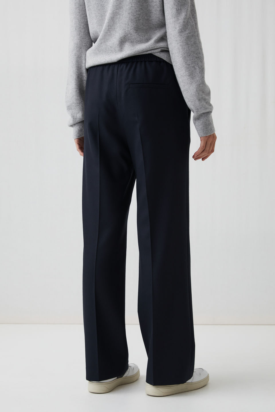 Model side image of Arket elastic waist wool trousers in blue