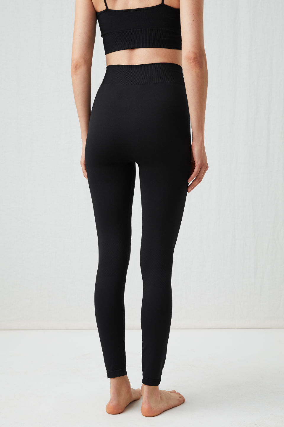 Model side image of Arket seamless yoga tights in black