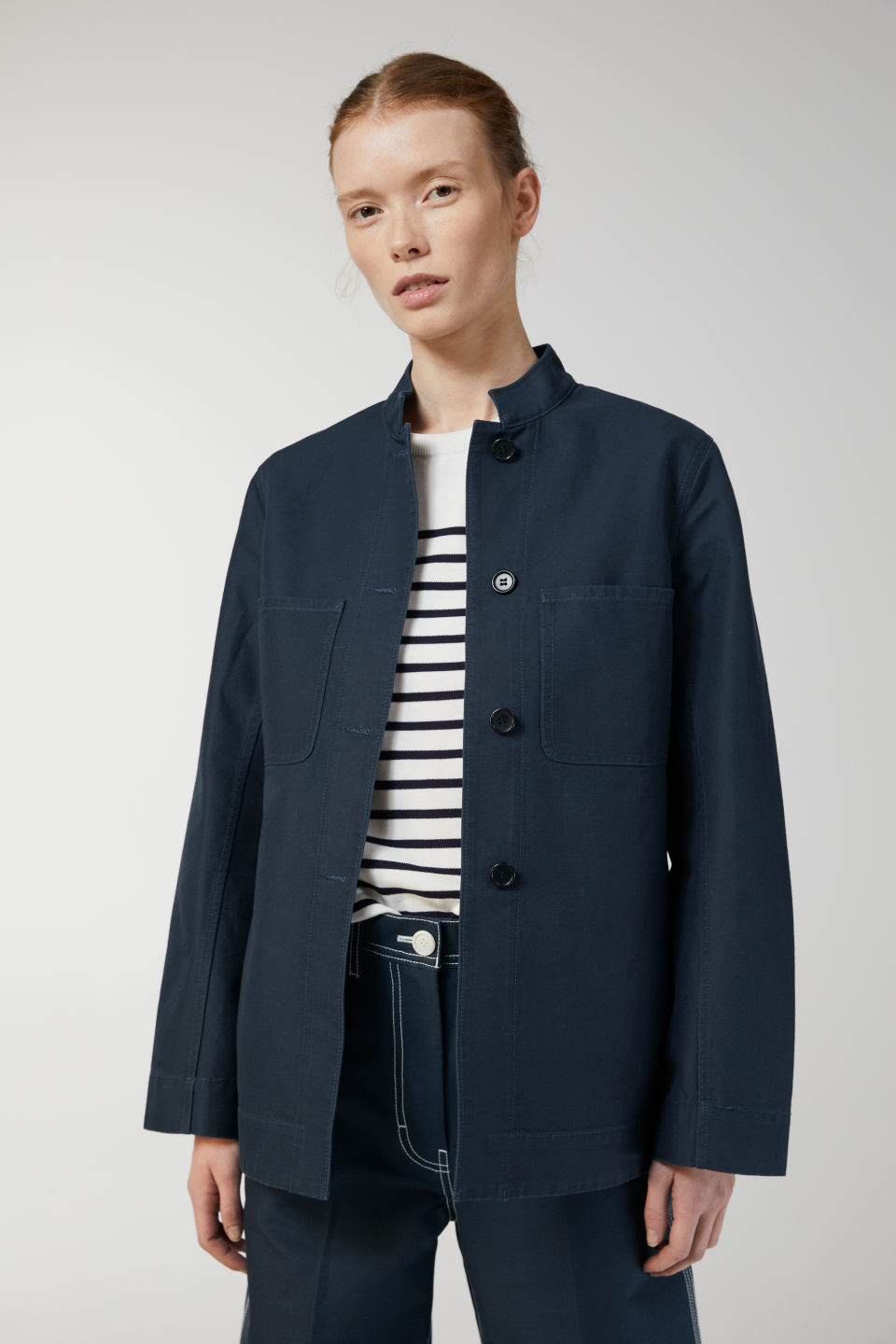 Model side image of Arket cotton workwear jacket in blue
